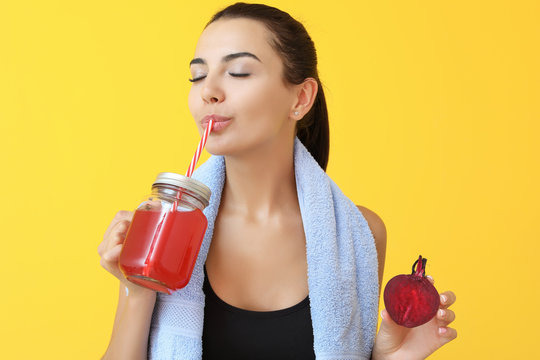 Young sporty woman drinking healthy beet juice on color background