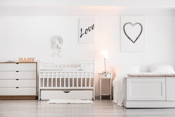 Stylish interior of modern bedroom with baby crib