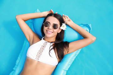 Beautiful young woman relaxing on inflatable mattress in swimming pool