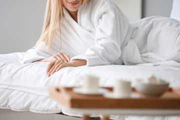 Wall Mural - Morning of young woman in bathrobe lying on bed