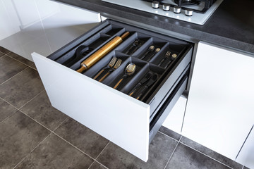 Opened drawer with cutlery inside, contemporary white grey kitchen in minimal loft style