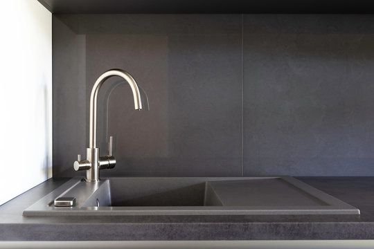Grey granite kitchen sink with a stainless steel tap for filtered water on a grey benchtop and grey backsplash.
