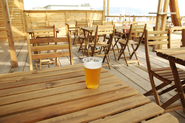 Plastic pint of beer on the table of a beach restaurant