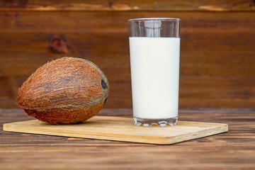 Coconut milk. A glass of skim milk next to coconut close-up on a wooden table.