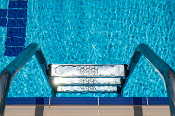 Wall Mural - Grab bars ladder in the swimming pool