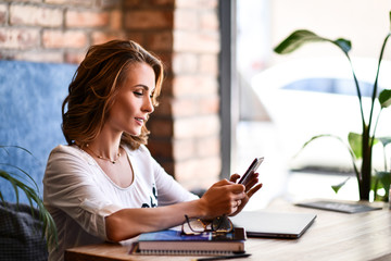Charming woman with beautiful smile reading good news on mobile phone during rest in coffee shop, happy Caucasian female watching her photos on cell telephone while relaxing in cafe during free time.