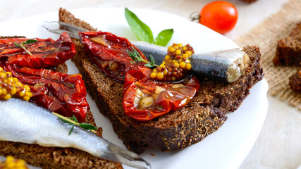 Tasty smorrebrod on a white plate. Sandwiches with black rye bread, sun-dried tomatoes, salted anchovies, mustard.