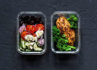Two healthy balanced lunch boxes with greek salad, baked chicken breast and broccoli on a dark background, top view