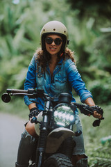 beautiful woman making a jungle tour with her motorcycle