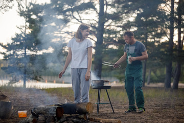 Tuinposter Ontspanning Happy man cooks barbecue meat grill outdoors in nature.