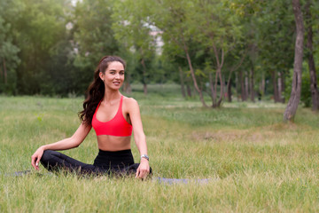 Young attractive smiling toned brunette woman doing yoga outside in a park. Healthy lifestyle...