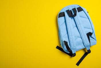 School blue backpack on yellow background, top view