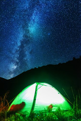 Space starry nights with a bright Milky Way on the backdrop of tourists with tents.