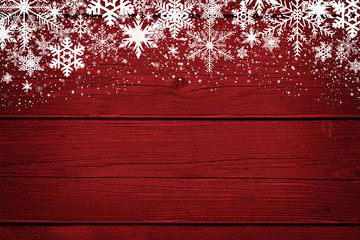Red Christmas winter background with snowflakes on wood