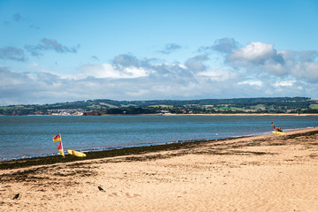 RNLI safe swimming area marked out by red and yellow flags and surfboards on Exmouth beach, Devon, England.