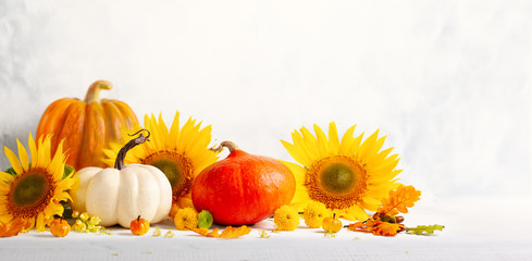 Beautiful autumn still life with sunflowers, red- yellow flowers, autumn leaves and white and orange pumpkins on wooden table, front view. Autumn concept with pumpkins and flowers.