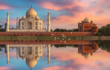 Fototapete - Taj Mahal Agra at sunset with water reflection and moody sky. Taj Mahal is a UNESCO World Heritage site on the banks of river Yamuna at Uttar Pradesh India.