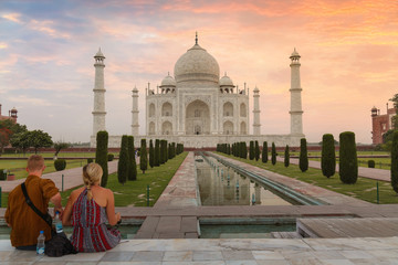 Fototapete - Taj Mahal at dawn with tourist couple enjoying a romantic moment at Agra India