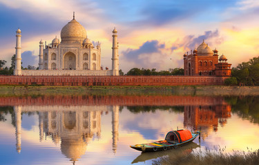 Wall Mural - Taj Mahal Agra at sunset on the banks of river Yamuna with moody sunset sky and view of wooden boat used for tourist ride on the river