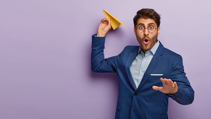 Image of prosperous busiessman holds paper aircraft, going to launch it, wears round spectacles and formal blue suit, poses against purple background with blank space. Shocked male entrepreneur