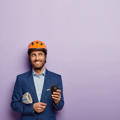Photo of handsome cheerful man with toothy smile, carries crumpled newspaper, holds takeout coffee, thinks about new successful building project, wears protective helmet, formal suit, poses indoor