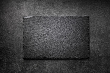Black slate board on dark stone texture top view. Empty space for menu or recipe.