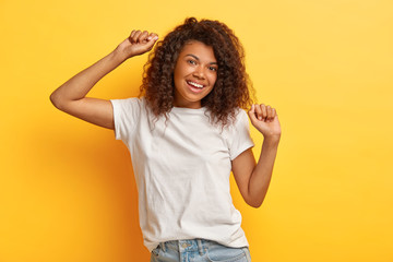 Photo of happy dark haired woman with positive expression, raises arms and moves while dancing, dressed in white casual t shirt and jeans, isolated over yellow background, has fun. Pleasant emotions