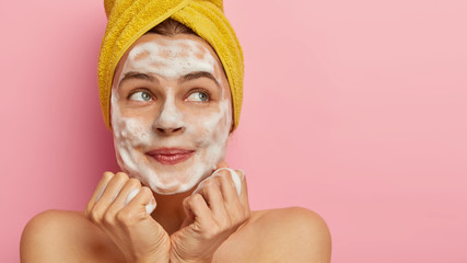 Cropped image of lovely young woman washes face with foaming soap, has pleased facial expression, keeps hands together under chin, has morning routine, stands against pink studio wall with blank space