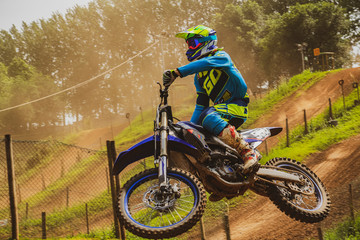 Sport motocross competition and motorcyclist in motion jumps
