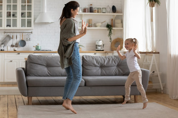 Full-length image mother dancing with preschool daughter at home