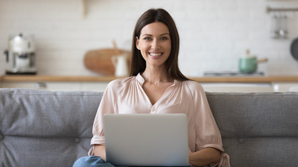 Woman sitting on couch holding computer looking at camera