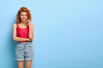 Isolated shot of thoughtful pleasant looking ginger woman with natural beauty, keeps hands partly crossed, looks aside dressed in casual outfit, isolated over blue wall copy space. Dreamy redhead girl