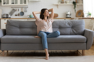 In cozy living room happy woman sitting on couch alone