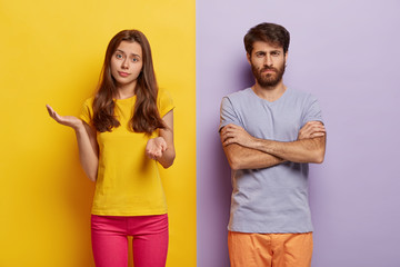 Hesitant young woman spreads hands with doubt, wears casual clothes, dissatisfied man keeps hands crossed, discontent with something, stands against two colored studio wall. Negative emotions