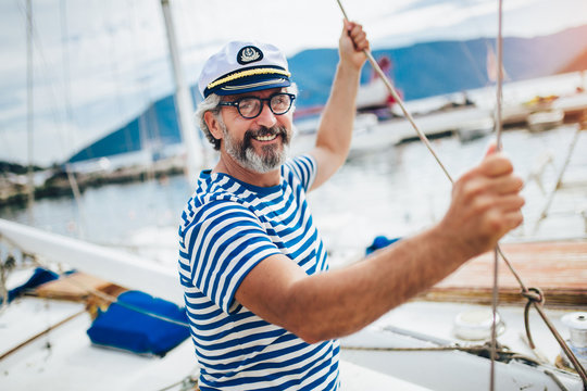 Mature man standing and laughing at helm of sailboat out at sea on a sunny afternoon.
