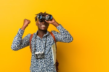 Young african tourist man standing against a yellow background holding a binoculars Fototapete