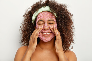 Image of happy pretty African American woman makes peeling of face with pink sea salt scrub, touches cheeks, stands bare shoulders against white background. Personal care and beauty concept.