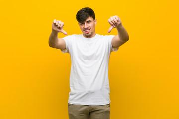 Young hispanic casual man showing thumb down and expressing dislike.
