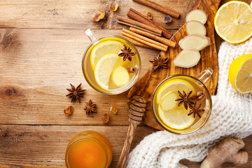 Healing ginger tea in two glass mug in scarf with lemon, honey and spices. Autumn hot drink on rustic wooden table top view.