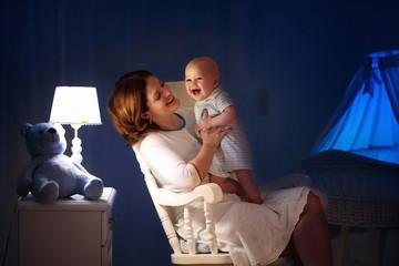 Mother and baby in dark bedroom
