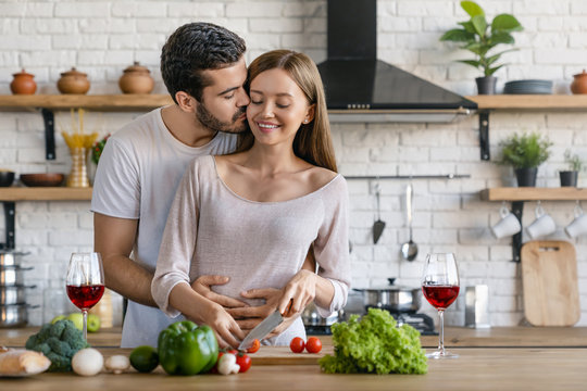 Beautiful cheerful young couple cooking dinner while man kissing his girlfriend standing in the kitchen at home