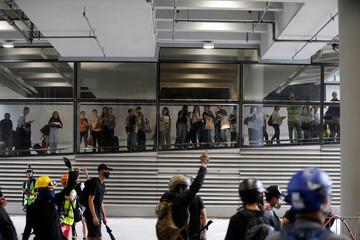 Passengers watch and take pictures of protestors at Hong Kong International Airport, in Hong Kong