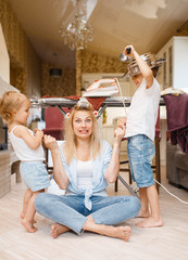 Young housewife with playful kids on the kitchen