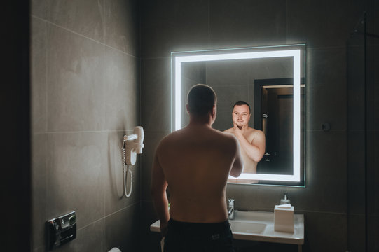A young groom stands in the bathroom near the mirror and is reflected. Portrait of a stylish man after shaving with a beautiful body and torso. Concept and photography.