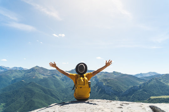 Young Man Hands Up Sitting on Top of a Mountain .