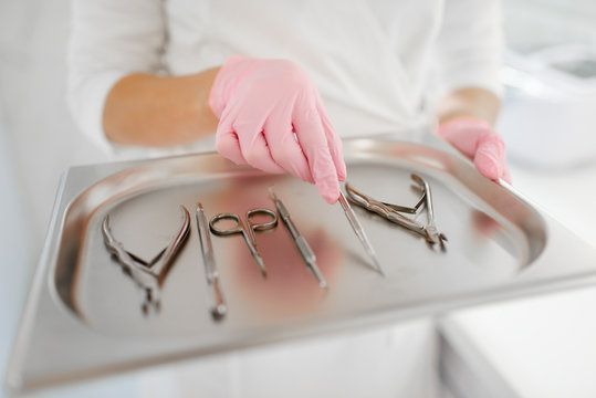Cosmetologist holds metal tray with equipment