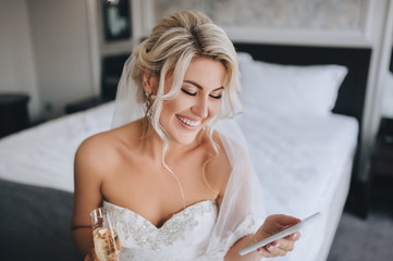 A beautiful, smiling blonde bride in a white dress is sitting on the bed and looking at the phone, reading a message and drinking champagne. Wedding portrait of a cheerful girl.