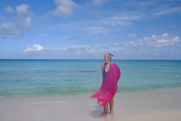 Retired Female in a bathing suit on an empty beach in the Grand Cayman islands during summer vacation