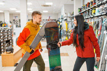 Couple buying downhill ski and snowboard, shopping