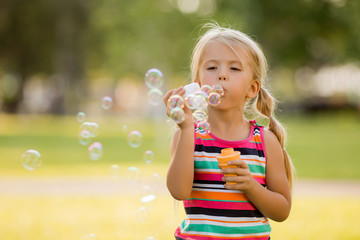 little blonde girl inflates soap bubbles in summer on a walk,  International children's day
